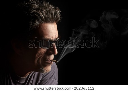 Smoking, Man with glasses and a cigar in mouth. Closeup portrait of half face over black background - stock photo