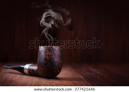 Smoking pipe on a wooden table - stock photo