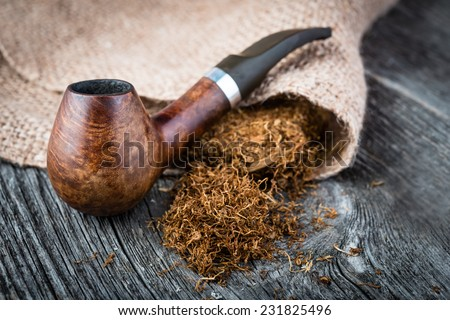 smoking pipe with  tobacco leaves on wooden background - stock photo