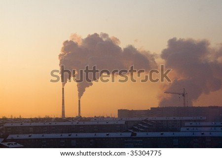 Smoking pipes of factory against a sunset