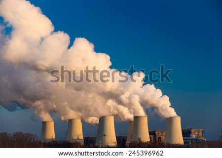 Smoking pipes of thermal power plant against blue sky on sunset - stock photo
