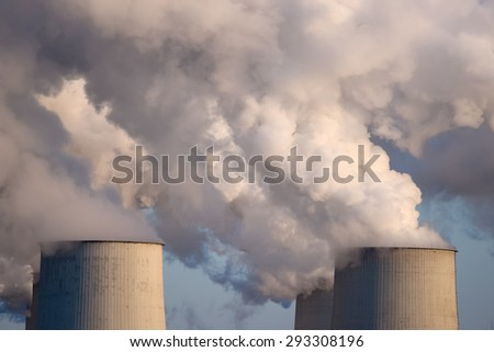 Smoking pipes of thermal power plant  on sunset. - stock photo