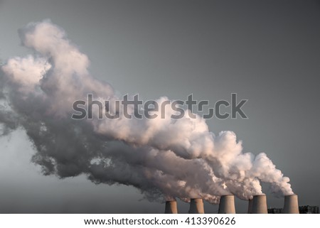 Smoking pipes of thermal power plant on sunset. /White balance changed/ - stock photo