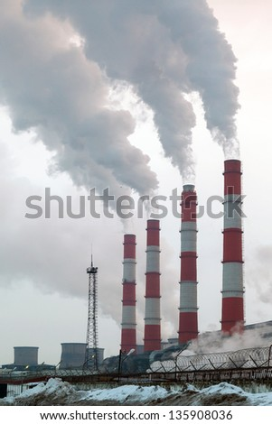 Smoking pipes of thermal power plant on the background of cloudy sky - stock photo