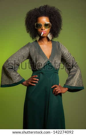 Smoking retro 70s fashion afro woman with green dress and sunglasses. Green background.