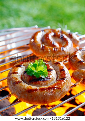 Smoking Rolled sausage on the grilling pan with open flames