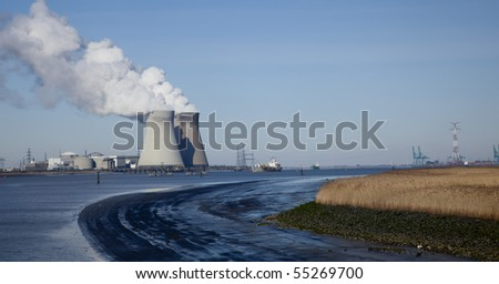 Smoking silos of the nuclear power plant near Antwerp, with boats floating by on the river - stock photo