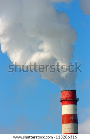 Smoking stack of the thermal power station against a blue sky - stock photo