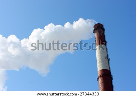 Smoking stack of thermal power station against a blue sky - stock photo