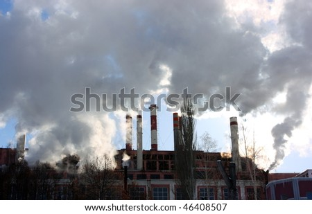 Smoking stacks of the thermal power station against a blue sky - stock photo