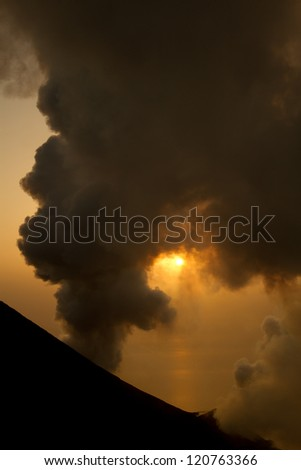 smoking volcano at sunset - stock photo