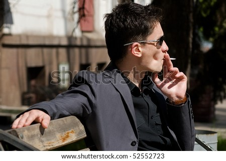 Smoking young man in sunglasses - stock photo