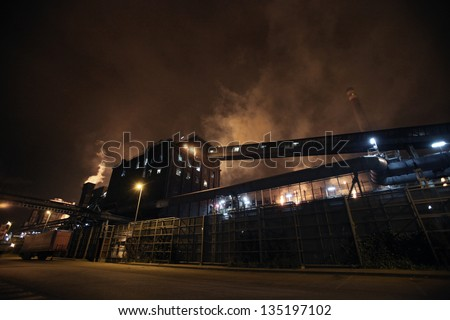 Smoky Factory At Night. Night view of a big factory in Avil�©s, Asturias, north of Spain, with smoky chimneys - stock photo