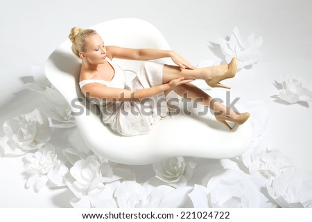 Smooth leather legs .Beautiful young woman sitting on a white chair surrounded by stylish white flowers  - stock photo