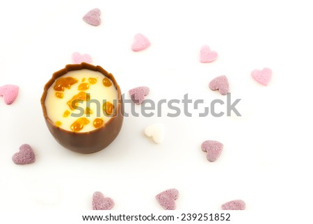 Smooth milk chocolate with a creamy caramel truffle center, decorated with crunchy caramel pieces. White background with tiny decorative sugar hearts - stock photo