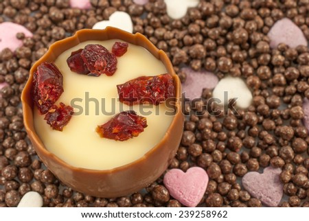 Smooth milk chocolate with an aromatic cherry brandy truffle center, decorated with sweetened dried cranberry pieces. Chocolate balls and small sugar hearts as background - stock photo