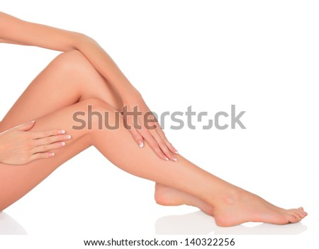 Smooth skin on female legs. White background, copyspace.  - stock photo