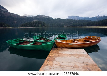 smooth water of mountain lakes and boats - stock photo
