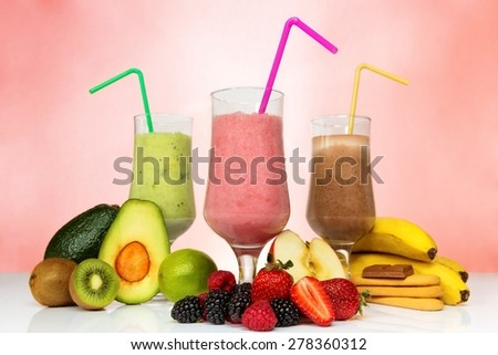 Smoothie concept. Fruit smoothies in different colors next to various fruits. - stock photo