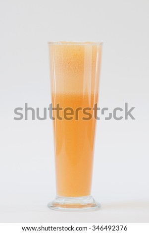 smoothie orange colour in tall glass on white background