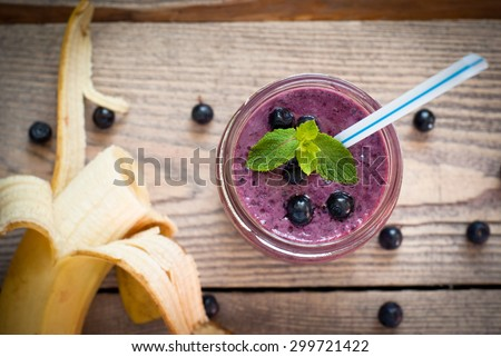 Smoothie with blueberries and banana in a glass jar with a straw - stock photo