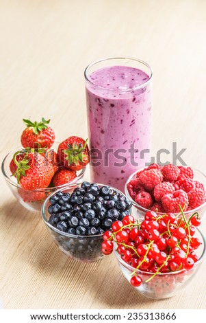 Smoothie with strawberry, red currant, blackberry and raspberry on table. - stock photo