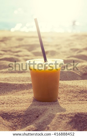 smoothies of tropical fruits on the sand sea beach (toning) - stock photo