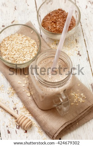 Smoothies with milk (soy, almond, coconut), oatmeal and flax seeds on a wooden background (top view) - stock photo