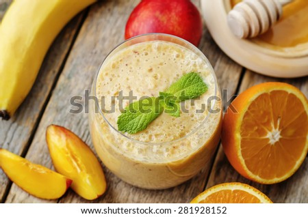 smoothies with peaches, banana and orange. the toning. selective focus - stock photo