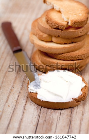 snack crackers with cream cheese and knife on wooden background - stock photo
