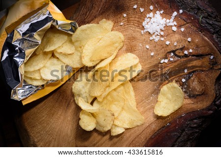 Snack of potato chips with sea salt over wooden background. Top view. - stock photo