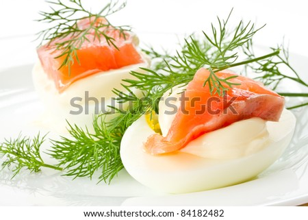 snack of salted eggs and trout on a plate - stock photo