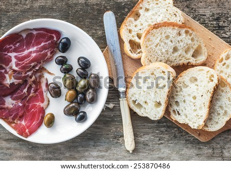 Snack set. Smoked meat or prosciutto and olives on a white plate, vintage knife and baguette slices over a rough wood background. Top view - stock photo