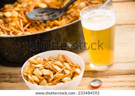 Snacks and Beer - This is a shot of a cold beer sitting next to a party mix. Shot on a wooden table. - stock photo