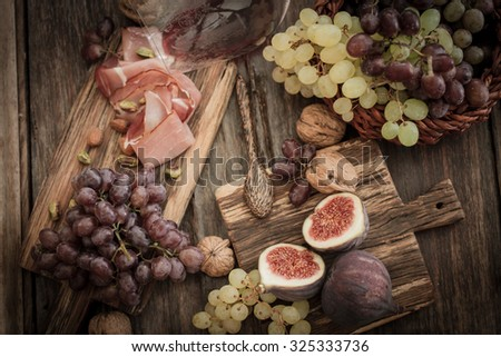 snacks for wine grapes in the form of dates and bacon, - stock photo