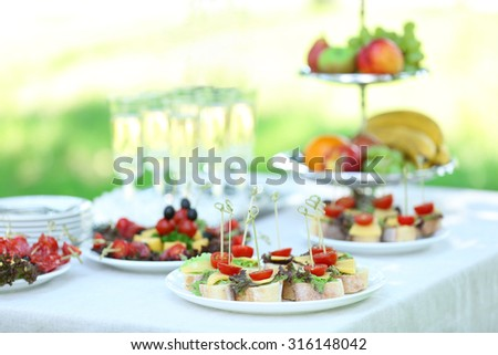 Snacks, fruits and drinks on table, outdoors. Garden party concept - stock photo