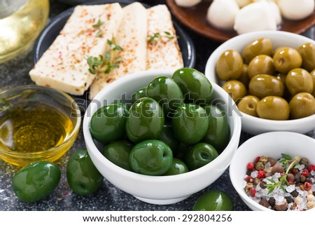 snacks - green olives and soft cheeses, close-up, horizontal - stock photo