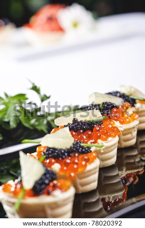 snacks with salmon roe and vegetables on a black plate - stock photo