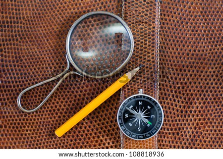 Snake leather texture with magnifying glass, compass and pencil - stock photo