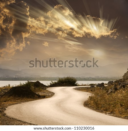snake road under dramatic sky with sun rays - stock photo