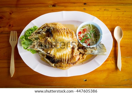 Snapper fish fried with fish sauce on wooden table
