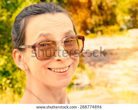 Snapshop of a smiling caucasian adult woman with large vintage sunglasses - stock photo