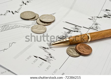 Snapshot of charts, coins, and a pen. - stock photo