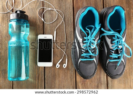 Sneakers and earphones on wooden table, top view - stock photo