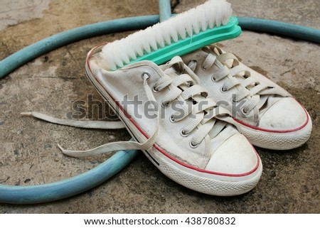 Sneakers are wash on a cement floor. - stock photo