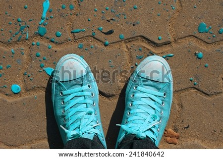 Sneakers from an aerial view on concrete block pavement. Top view. - stock photo