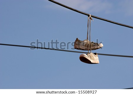 Sneakers hanging on a phone wire by a Los Angeles street gang to mark heroin drug sale area - stock photo