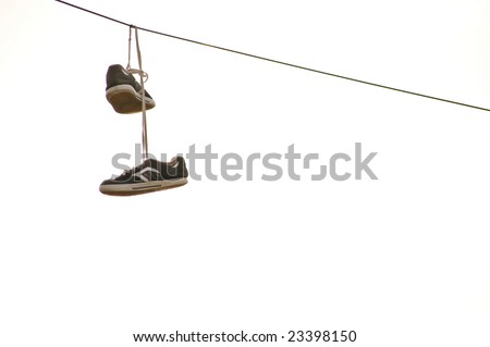 Sneakers hanging on wire - stock photo