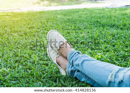 sneakers on girl legs on grass during sunny serene summer day - stock photo