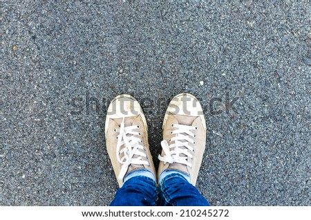 Sneakers shoes walking on concrete top view , Canvas shoes walking on concrete - stock photo
